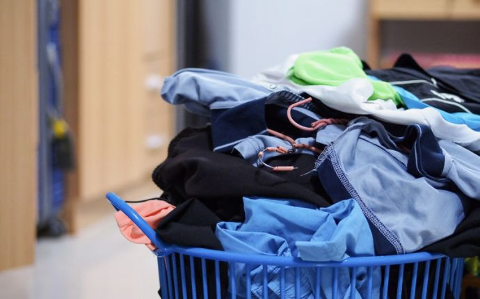 A blue laundry basket overflowing with clothes.