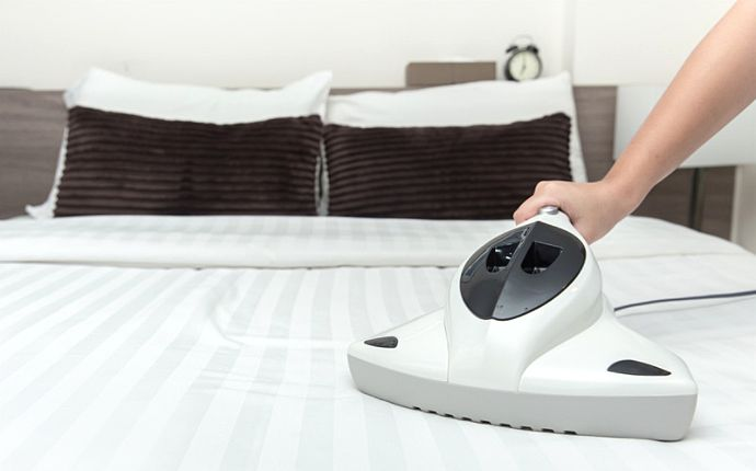 A handheld vacuum cleaner on striped white bedding.