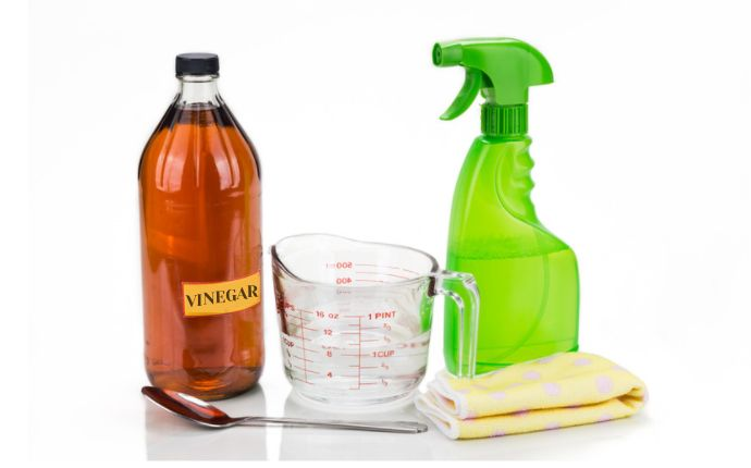 A bottle of vinegar, a measuring cup, a spoon, a yellow cloth, and a green spray bottle